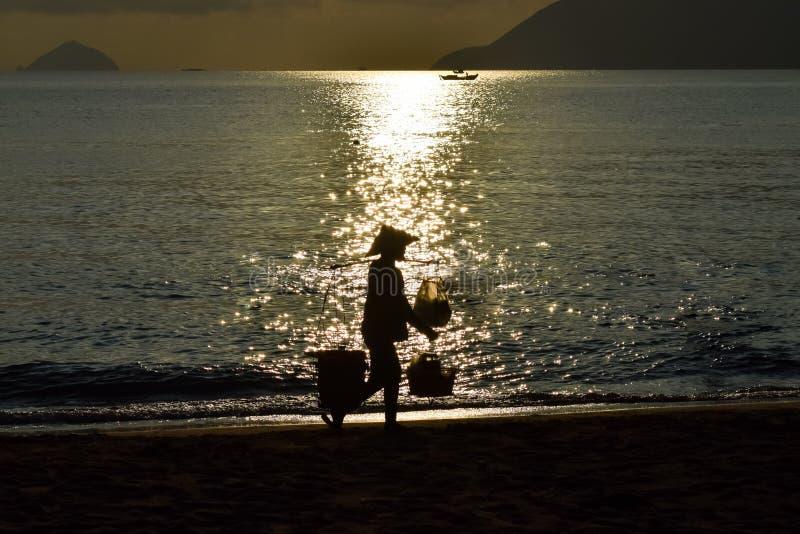 Silhueta do vendedor do alimento contra a reflex?o do feixe do sol na praia no alvorecer fotos de stock