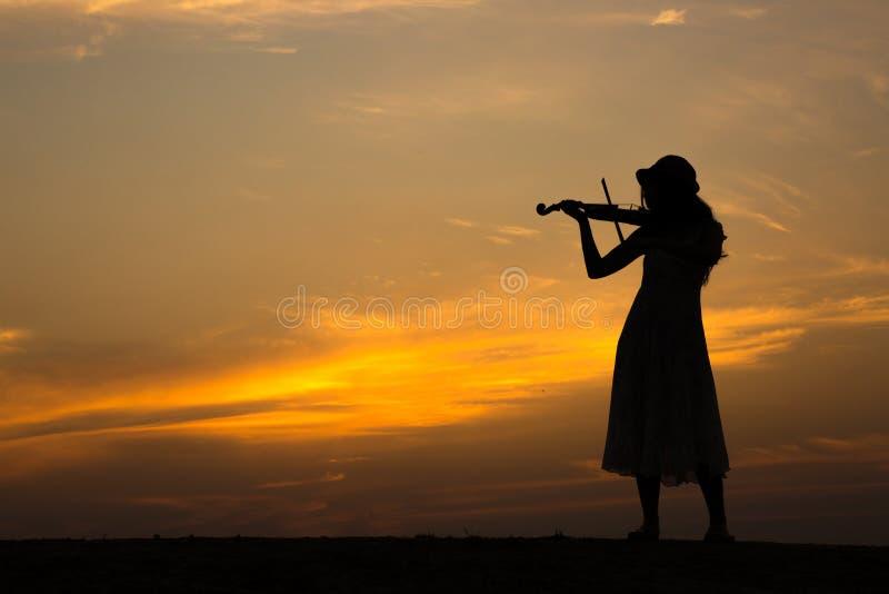 Silhueta do violino asiático do jogo da mulher imagens de stock