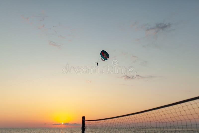 Silhueta do voo crescente posto do paraglider sobre o aga do mar imagens de stock