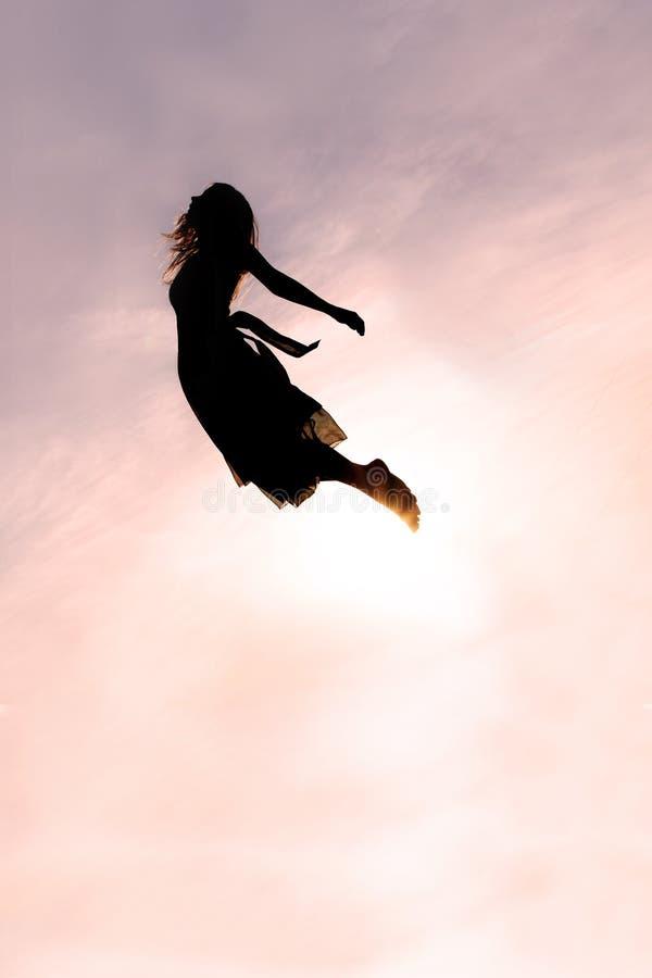 Silhueta do voo da mulher através do céu imagens de stock