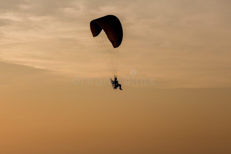 Silhueta do voo de Paramotors ao céu no voo extremo ativo do piloto do esporte do homem da aventura do por do sol no céu com glid fotografia de stock royalty free