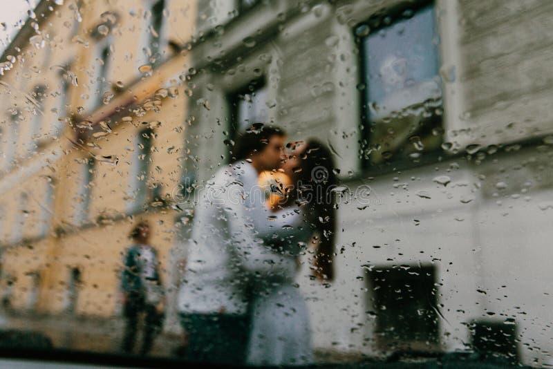 Silhueta dos amantes borrados que beijam na rua da cidade Vista da janela de um carro ou de um café imagem de stock royalty free