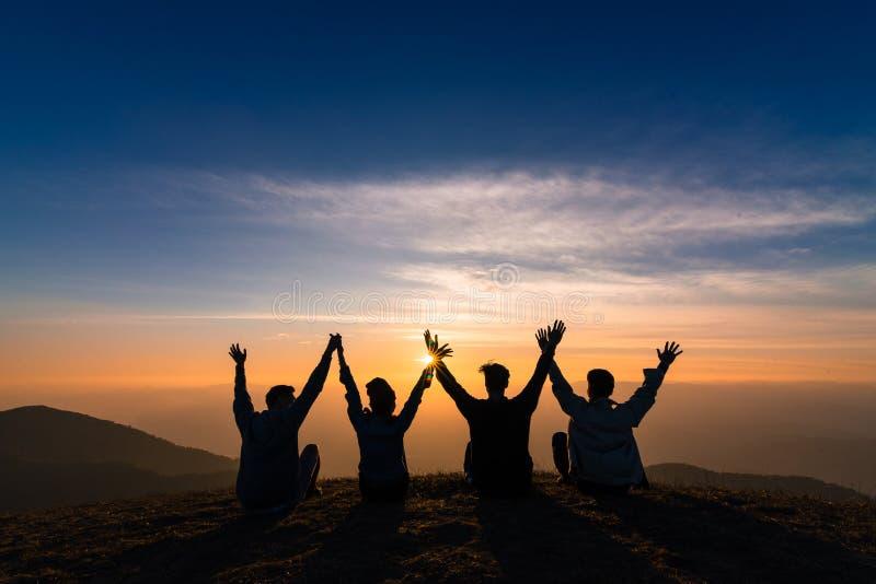 A silhueta dos amigos agita as mãos acima e sentando-se junto no sol fotos de stock
