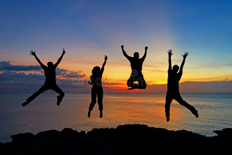 Silhueta dos amigos e dos trabalhos de equipa que saltam na praia durante o tempo do por do sol para o negócio do sucesso foto de stock royalty free