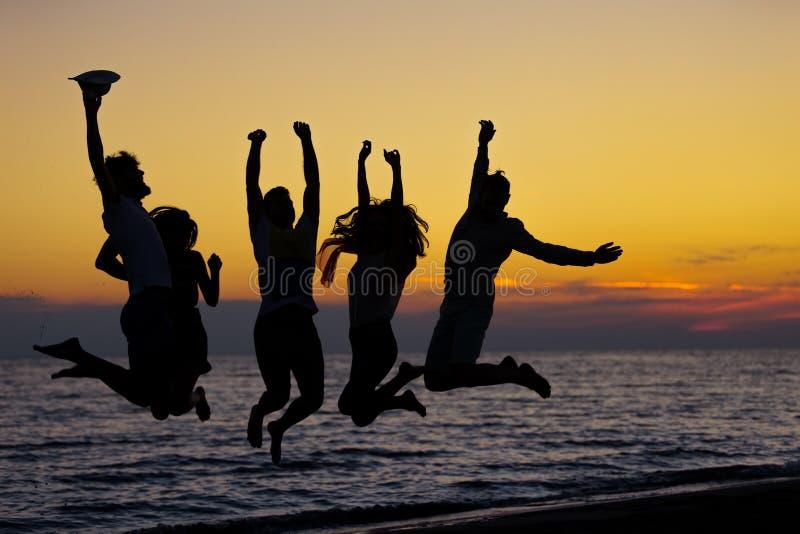 Silhueta dos amigos que saltam na praia durante o tempo do por do sol foto de stock royalty free