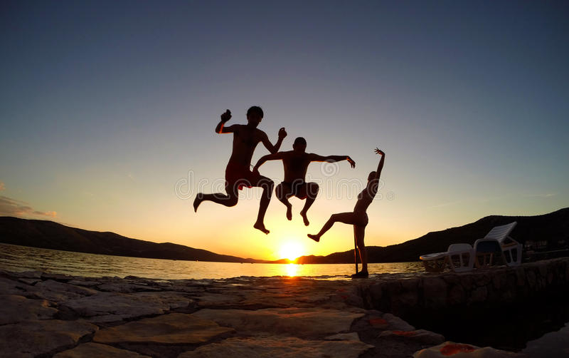Silhueta dos amigos que saltam no por do sol na praia imagem de stock royalty free