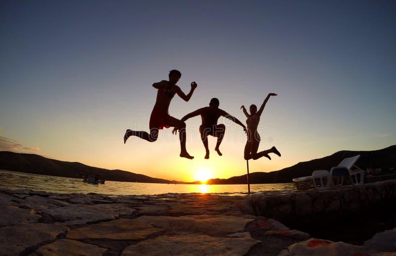 Silhueta dos amigos que saltam no por do sol na praia fotos de stock