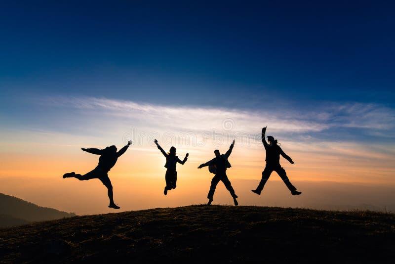 Silhueta dos amigos que saltam no por do sol para a felicidade, o divertimento e o te imagem de stock royalty free
