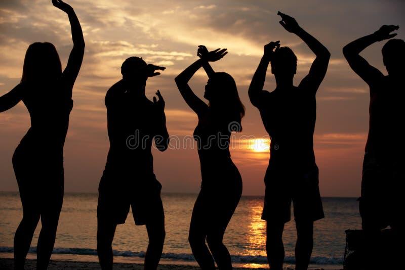 Silhueta dos amigos que têm o partido da praia foto de stock