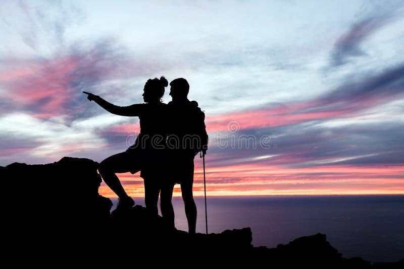 Silhueta dos caminhantes dos pares nas montanhas fotografia de stock royalty free