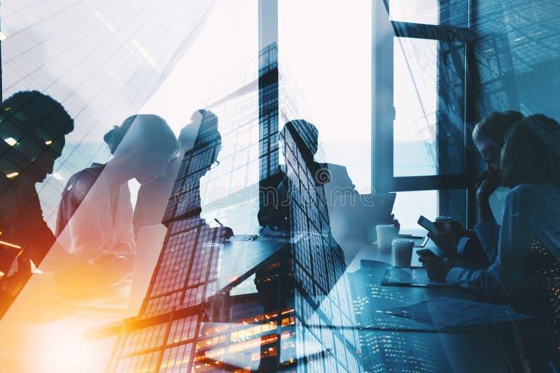 A silhueta dos executivos trabalha junto no escritório Conceito dos trabalhos de equipa e da parceria exposição dobro com luz fotografia de stock
