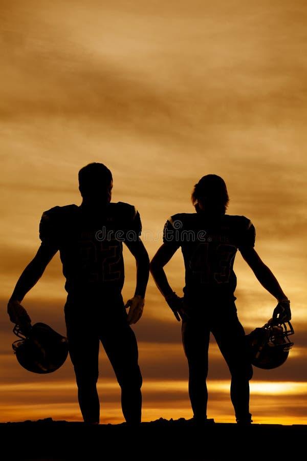 Silhueta dos jogadores de futebol que guardam capacetes no por do sol fotografia de stock royalty free