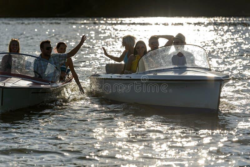 Silhueta de amigos novos nos motorboats imagens de stock