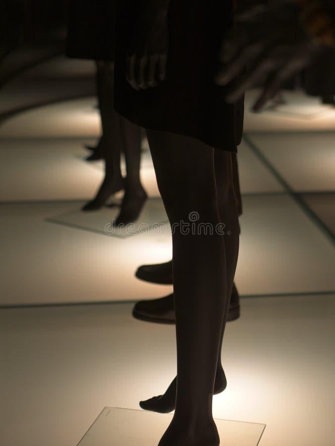 Silhueta dos manequins da forma que estão no assoalho iluminado fotografia de stock royalty free