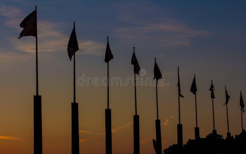 Silhueta dos mastros de bandeira no por do sol foto de stock royalty free