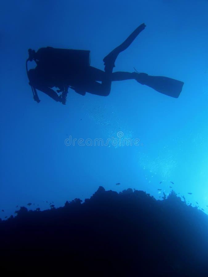 Silhueta dos mergulhadores fotografia de stock