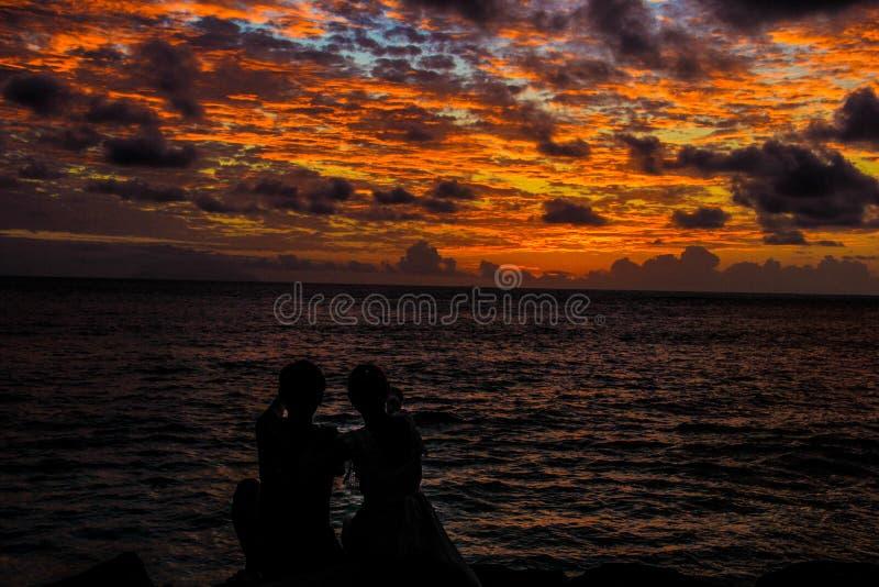 Silhueta dos pares do por do sol da praia de Seychelles Praslin Castello fotografia de stock