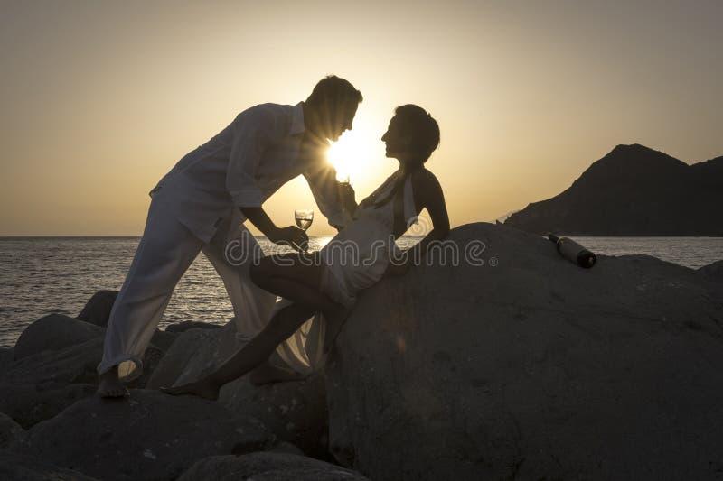 A silhueta dos pares felizes novos que têm o divertimento na praia balança no nascer do sol fotos de stock royalty free