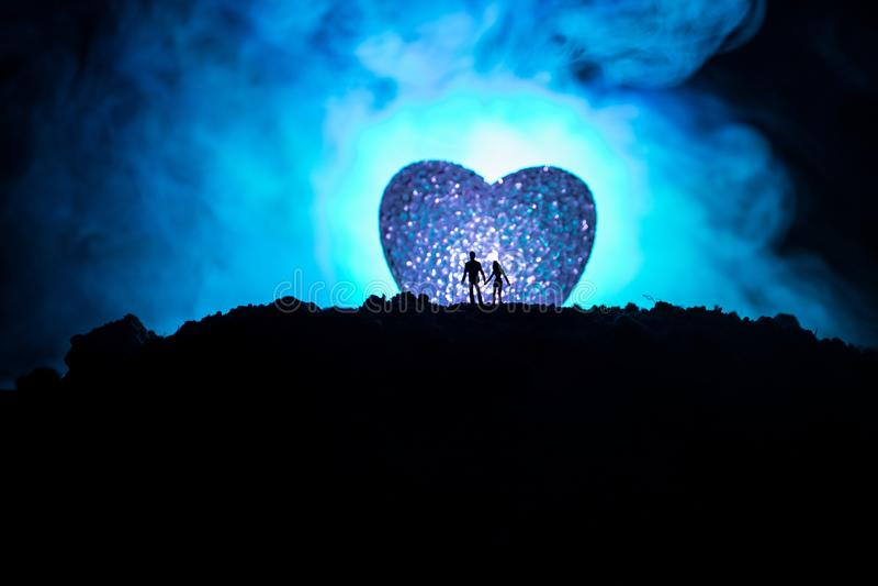 Silhueta dos pares felizes que estão atrás do símbolo dado forma grande do coração na montanha na noite O coração grande gosta da ilustração do vetor