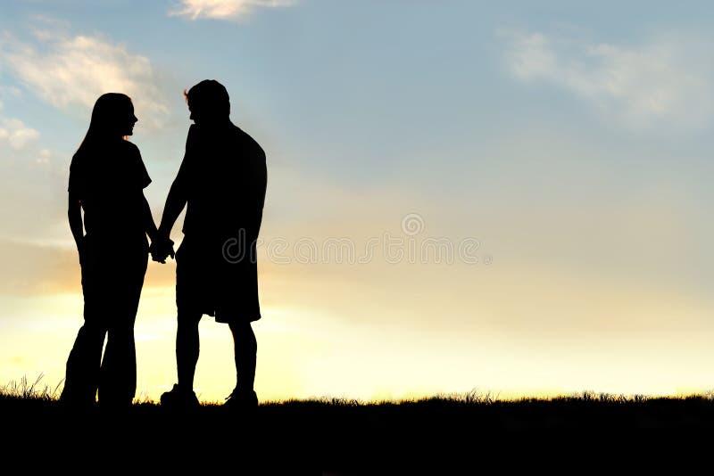 Silhueta dos pares felizes que guardam as mãos e que falam no por do sol fotografia de stock royalty free