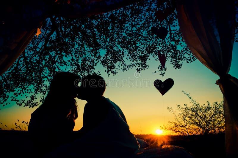 Silhueta dos pares no amor que beija no por do sol