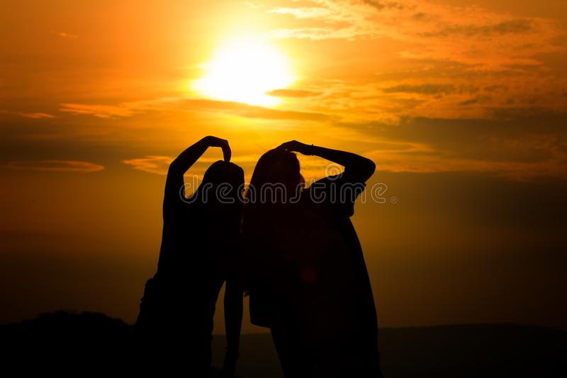 Silhueta dos pares no amor que olha um por do sol nas montanhas, foto de stock