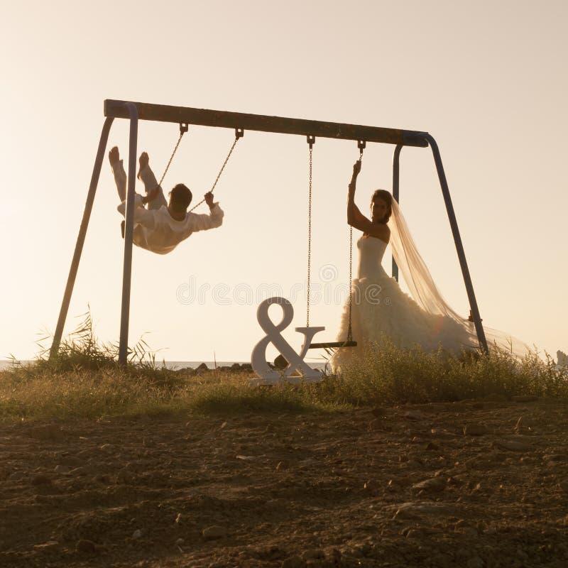 A silhueta dos pares novos que jogam no balanço ajustou-se no por do sol fotografia de stock royalty free