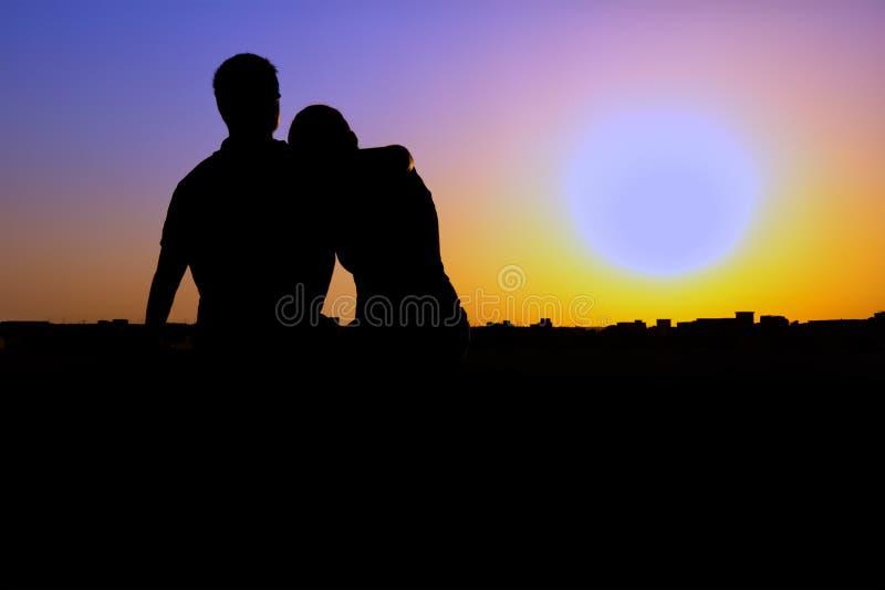 Silhueta dos pares que prestam atenção ao por do sol fotografia de stock