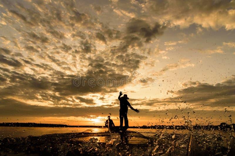 Silhueta dos pescadores com tempo do por do sol no distrito de Wanon Niwat fotos de stock