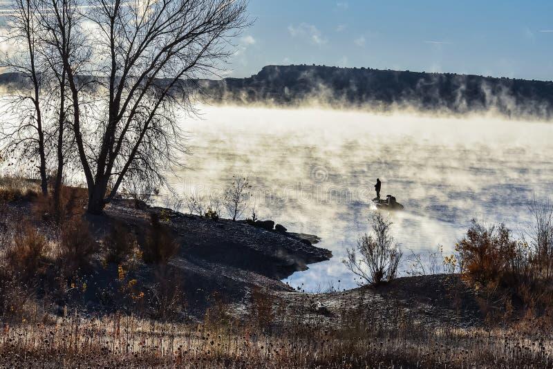 Silhueta dos pescadores contra o amanhecer Sun e a névoa fotos de stock