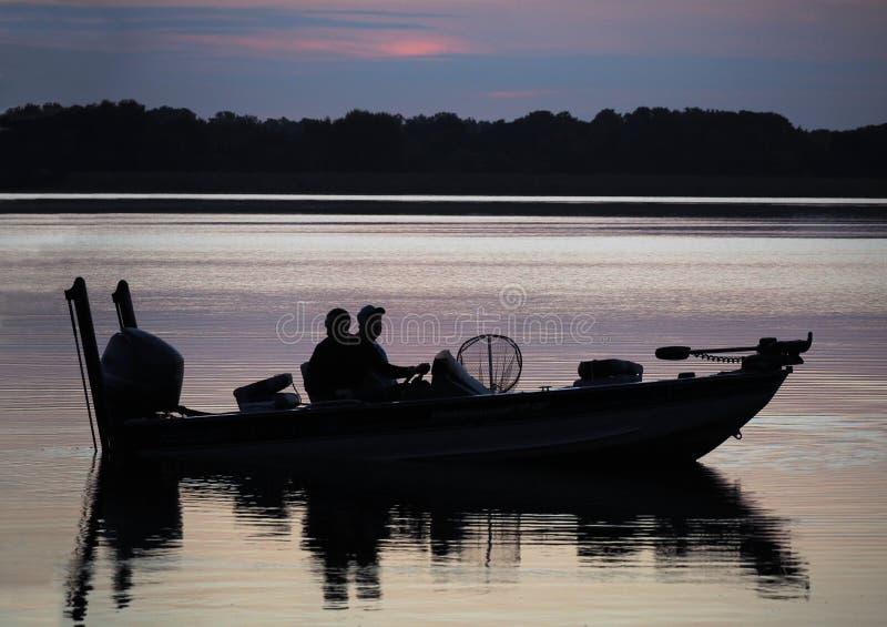 Silhueta dos pescadores no barco no nascer do sol imagem de stock