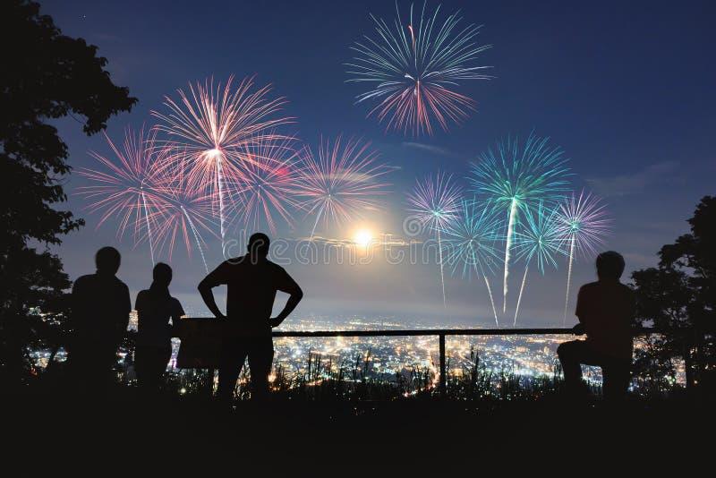A silhueta dos povos aprecia olhar o fogo de artifício fotografia de stock