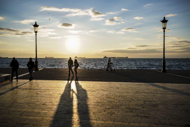 Silhueta dos povos que andam no por do sol pelo mar fotografia de stock