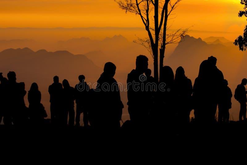 A silhueta dos povos relaxa no penhasco e nas montanhas com por do sol na noite imagens de stock royalty free
