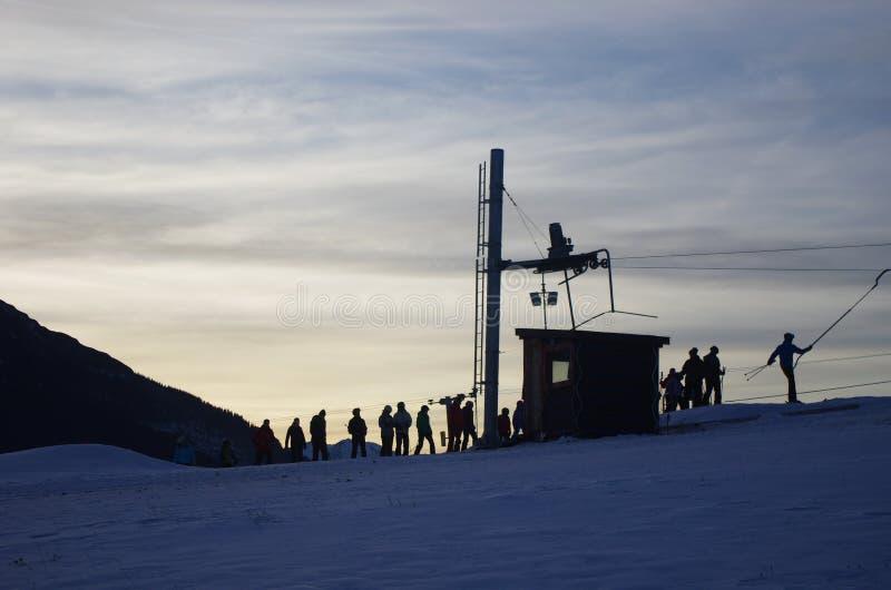 Silhueta dos reboques de esqui com os povos em Vysoke Tatry em Eslováquia imagem de stock