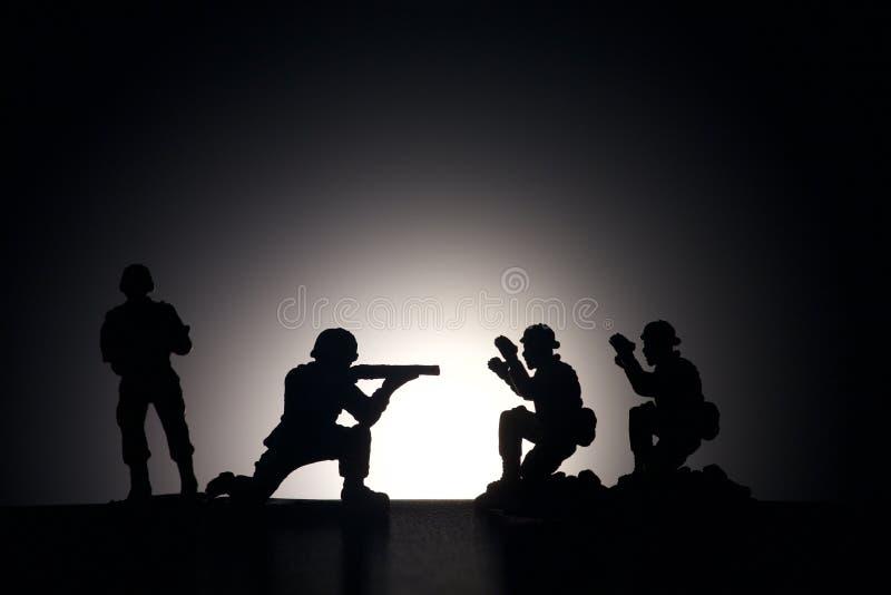 Silhueta dos soldados em um fundo escuro imagem de stock