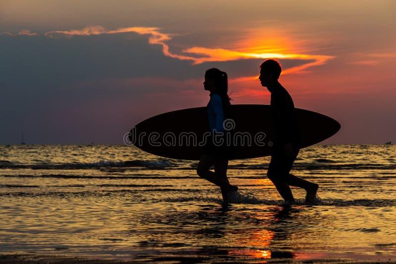 Silhueta dos surfistas do homem e da menina que correm ao mar com ressaca imagens de stock