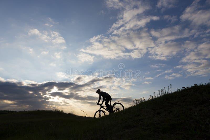 Silhueta e Mountain bike do homem do ciclista foto de stock royalty free