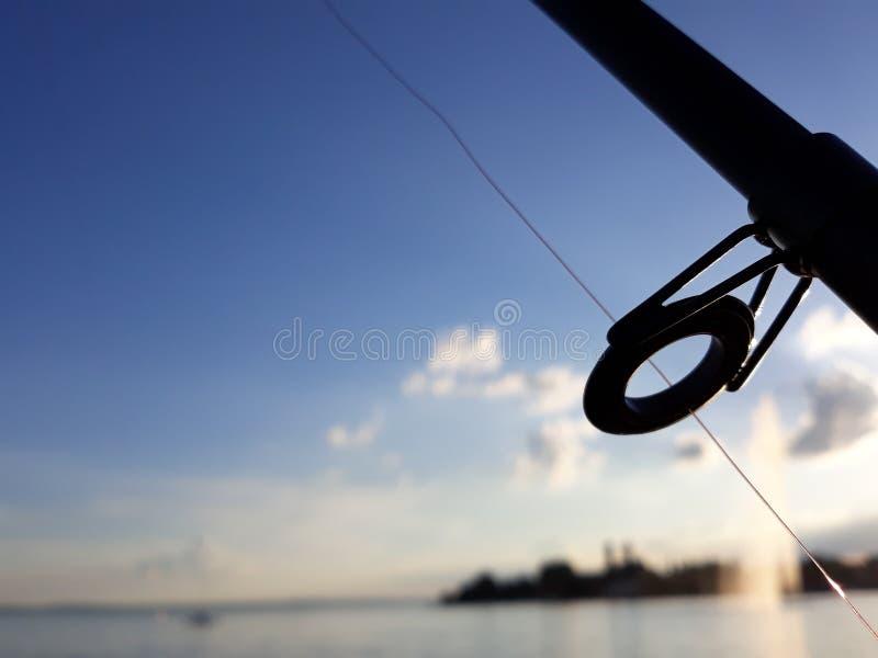 Silhueta e porto da vara de pesca atrás dele fotos de stock