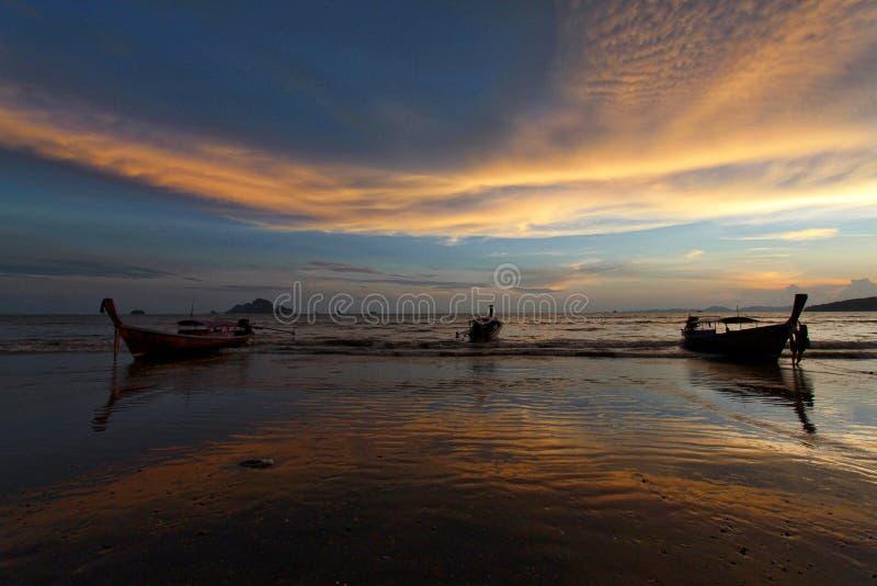 Silhueta e reflexão do barco contra o céu do por do sol foto de stock