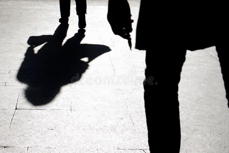 Silhueta e sombra obscuras de uma mulher que levam um saco e de um homem fotografia de stock