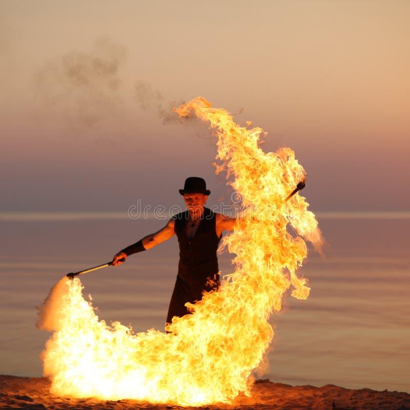 Silhueta elegante do dançarino que rodopia o bastão do fogo foto de stock