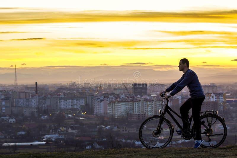 Silhueta escura de um homem que está perto de uma bicicleta com a noite foto de stock royalty free