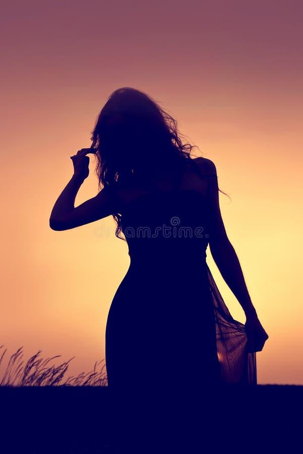 Silhueta escura de uma jovem mulher com cabelo longo que anda no l foto de stock
