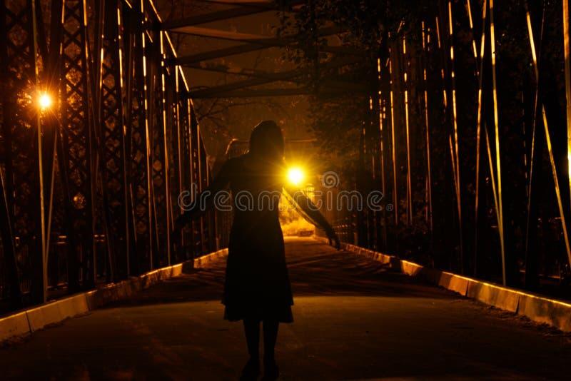 Silhueta escura em uma ponte escura fotografia de stock