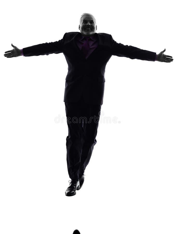 Silhueta estendido de salto superior dos braços do homem de negócio fotos de stock royalty free