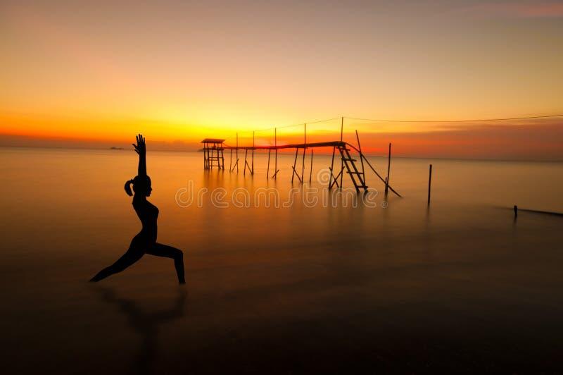 Silhueta exterior da ioga da praia fotos de stock royalty free