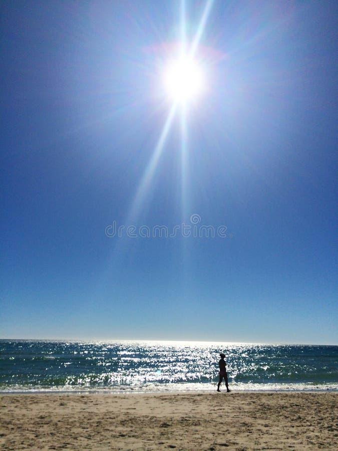Silhueta fêmea da cena da praia contra o sol da tarde imagens de stock