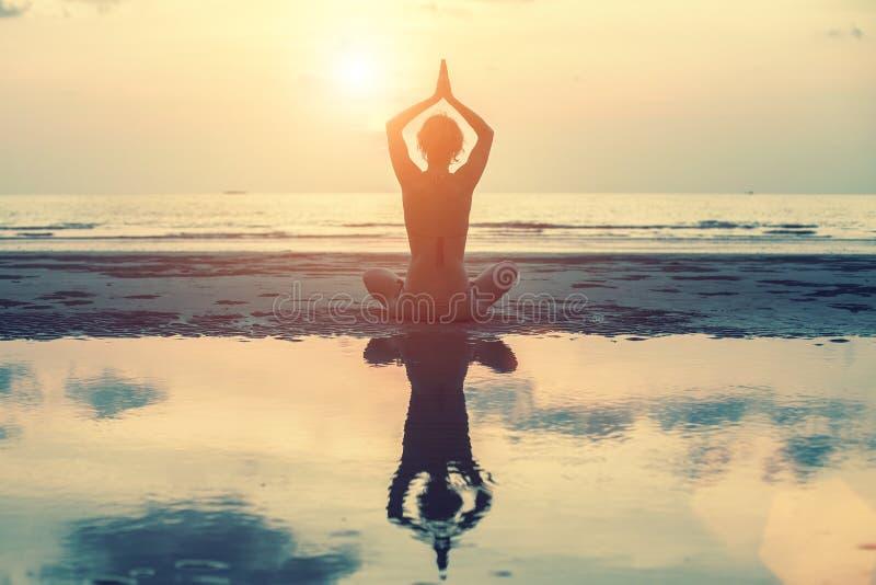 Silhueta fêmea na ioga com reflexão na água, pose da meditação no por do sol foto de stock