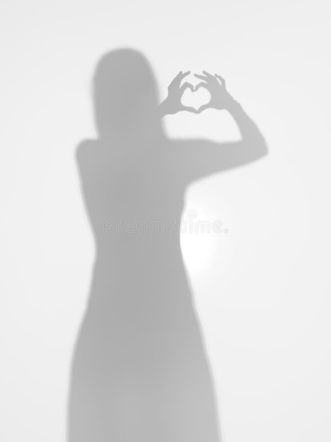 Silhueta fêmea que faz uma forma do coração com suas mãos imagem de stock royalty free